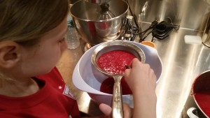 Straining raspberry puree to get out the seeds