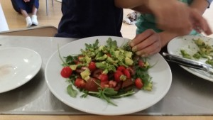 Working on the avocado, arugula, tomato salad.