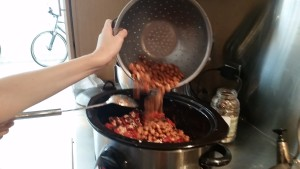 Adding the beans into the chili slow cooker.